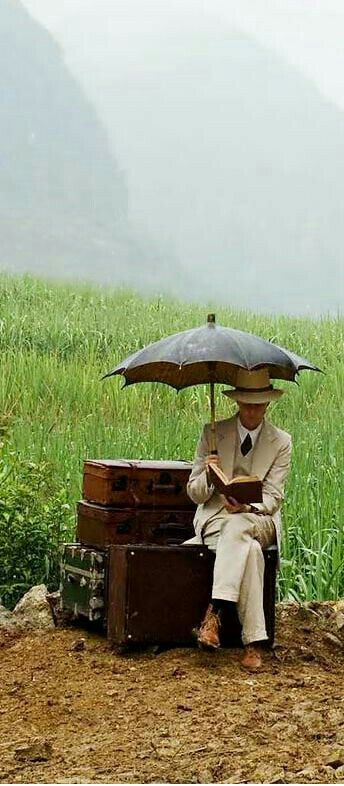 Photography | Man under umbrella, sitting on his suitcases, reading a book