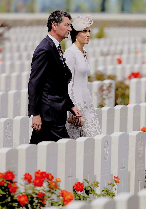 The Duchess of Cambridge and Vice Admiral Sir Timothy Laurence walk through the Commonwealth War Graves Commission's Tyne Cot Cemetery.