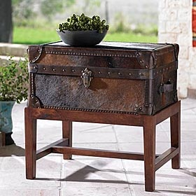 COWHIDE TRUNK & STAND  #208817  Cowhide covers this versatile trunk with leather trim accent. Use the storage compartment for linens or books, and use the top as an end table. Hardwood stand included. Hair on hide colors will vary. Exclusive to King Ranch. Imported. Allow 2-4 weeks for delivery.
