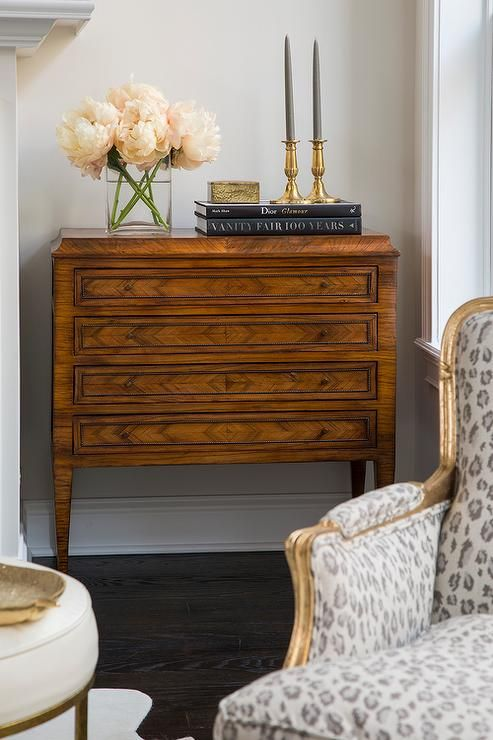 Chic living room nook is filled with a diamond pattern chest topped with flowers and black coffee ...