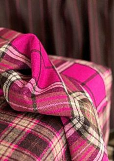 Vibrant pink throw on tartan chair