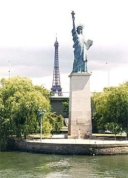 """A smaller-scale copy of the Statue of Liberty is found in Paris, France, where it stands near the Grenelle Bridge on the Île des Cygnes, an island in the river Seine.  It looks towards the Atlantic Ocean and hence towards its """"larger sister"""" in New York Harbor."""