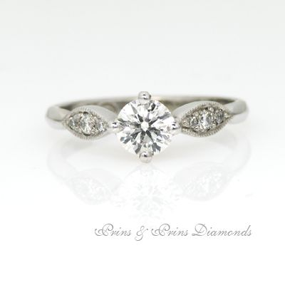 Stunning vintage style 4 claw solitaire set with diamonds on the side