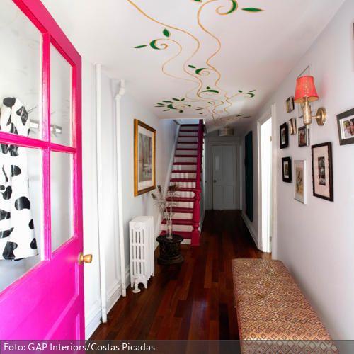 Eine Pinkfarbene Tür, Schnörkelbemalung An Der Decke, Kreativ Angebrachte  Bilderrahmen, Rot Angestrichene Treppenstufe