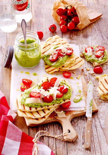 Selbst gebackene Brotfladen mit grünem Pesto, Tomaten und Parmesan obendrauf - das kann ja nur lecker schmecken!