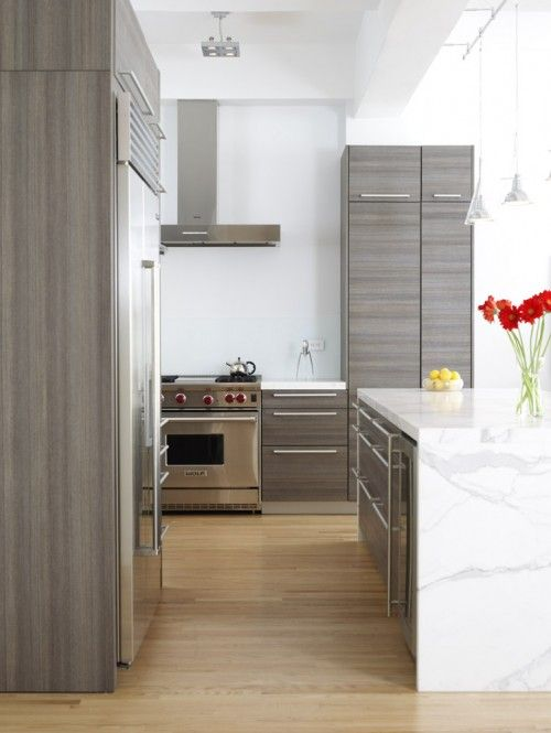 grey bamboo laminate cabinets, contemporary doors and drawer fronts and large drawers for pots and pans next to the stove, waterfall granite countertop that looks a bit like Carrara marble, blonde engineered wood floor