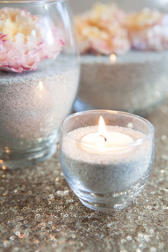DIY flower and sand centerpieces.  Use silk flowers from Afloral.com and you won't have to worry about your flowers wilting, AND you get a cute decoration you can keep in your home after the event.  Find sand, candles, and clear glass containers at Afloral.com.