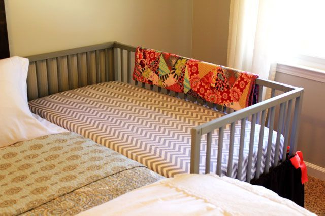 DIY Co-sleeper: The crib is securely attached to the bed frame with nylon straps! They bought a regular assembly-required crib and left one side off.