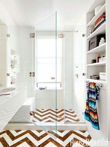 A Chevron marble floor in a luminous, all-white New York City bathroom.