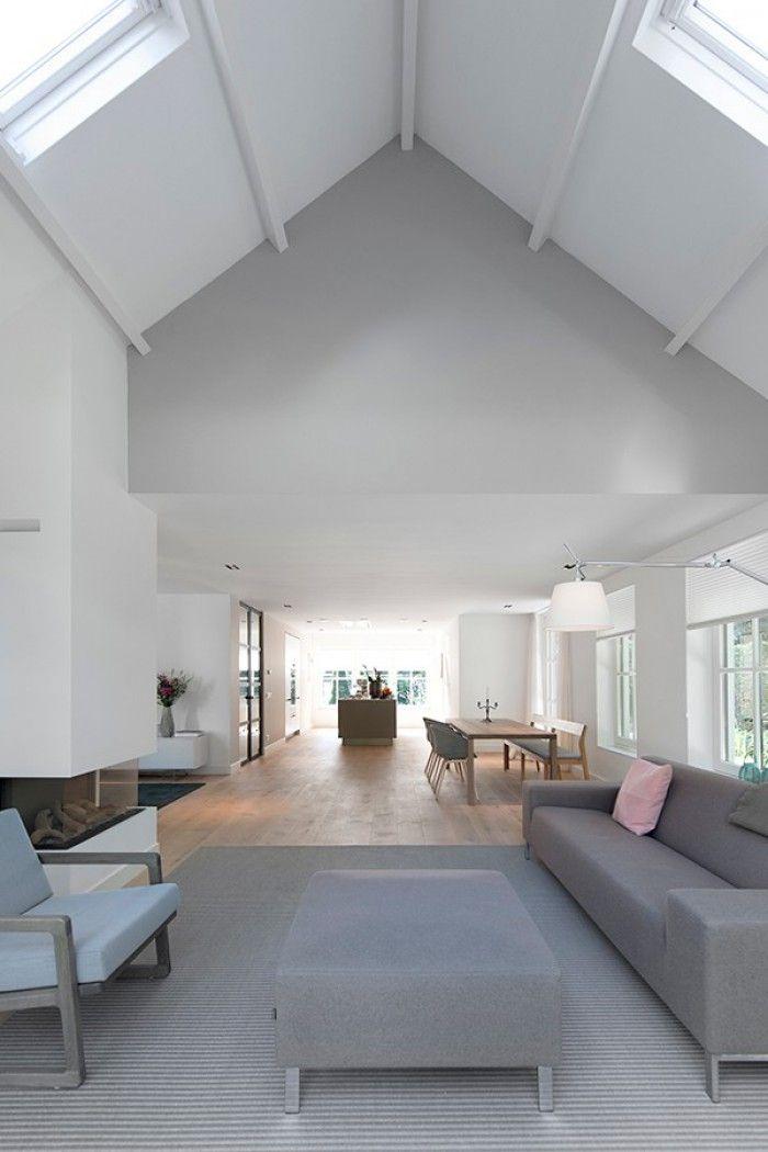 Woonkamer met plafond tot in de nok, open haard en open verbinding met keuken