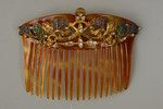 26 PLIQUE A JOUR MOUNTED CELLULOID HAIR COMB, c. 1900 Set with clear paste jewels in a floral motif, the clear enamel in blue, green and lilac. 3 x 4 1/2 inches. Excellent. $460.00