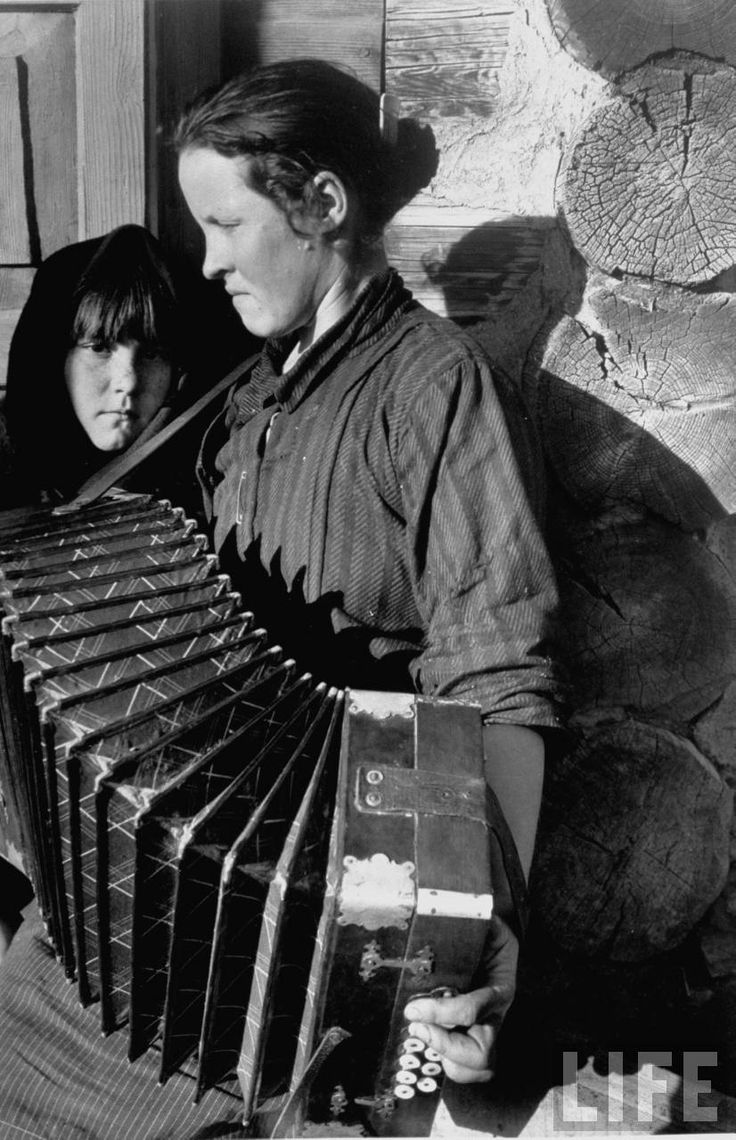 Woman playing a button accordion as her young daughter looks on, Magnitogorsk, 1931, by Margaret Bourke-White