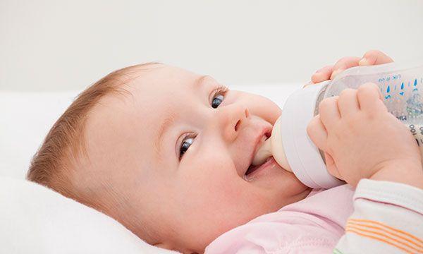 Baby happily sucking on sanitized bottle