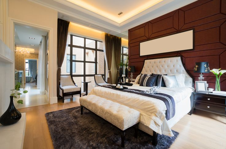 Luxurious master bedroom with wood paneled wall, all-white bed, light wood floor and stylish sitting area