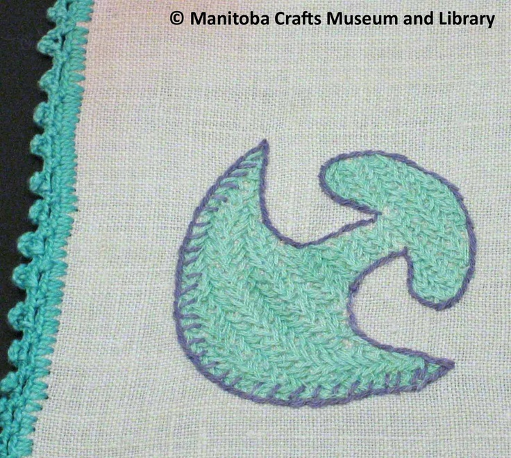 Detail: Embroidered placemat with scalloped edges. An Ulu or Women's Knife in the corner.