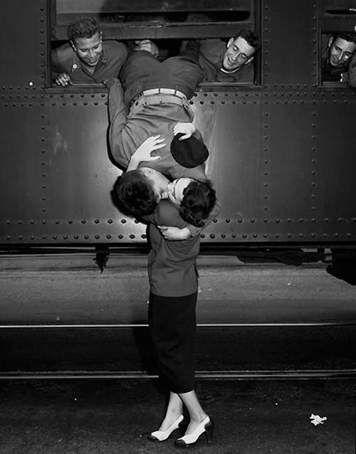 California, 1950 - A soldier leans out of a train to kiss a woman goodbye.