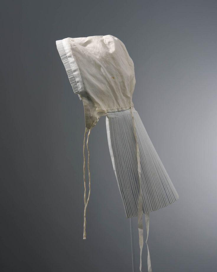 knipmuts voor in de rouw uit Vriezenveen, voor 1963. Knipmuts van wit effen katoen. De gepijpte voorstrook van 2,5 cm. wordt door laitondraad in vorm gehouden. Aan de binnenkant van de muts is achter de voorstrook een reepje zwart tibet gezet. De 21 cm. lange staart is zeer sterk geplooid. #Overijssel #Salland #Saksen