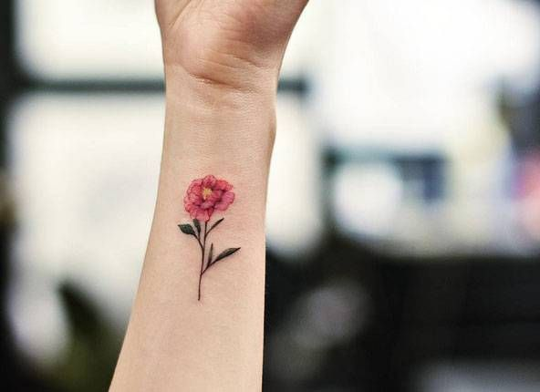 Pink peony flower tattoo on the wrist.