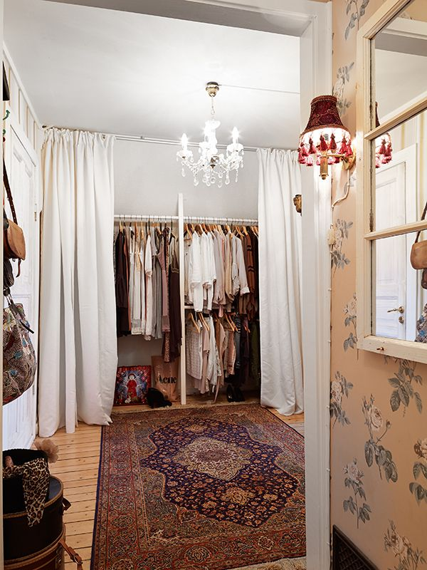 Scandinavian maximalist closet, complete with Persian rug, floral wallpaper, and tasseled sconce