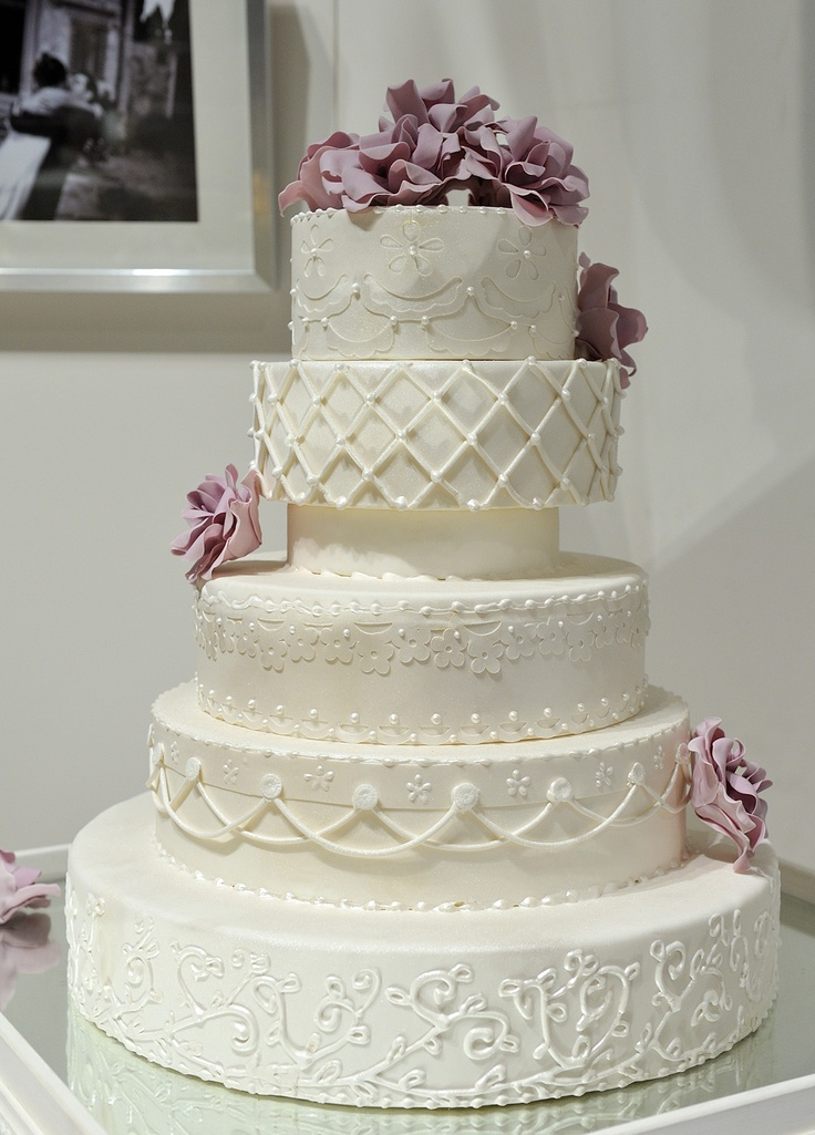 This 5 1/2 tier all white wedding cake was inspired by different patterns of eyelet lace for a wedding in Italy.