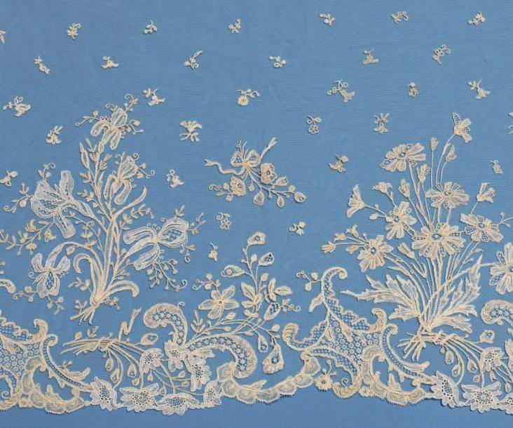 Beau volant de bas de robe, Duchesse de Bruxelles, aiguille et fuseaux, vers 1890. Riche décor de bouquets d'iris au point de gaze à l'aiguille et gerbes de fleurs au naturel aux fuseaux. Fleurons en… - Maigret (Thierry de) - 01/03/2017