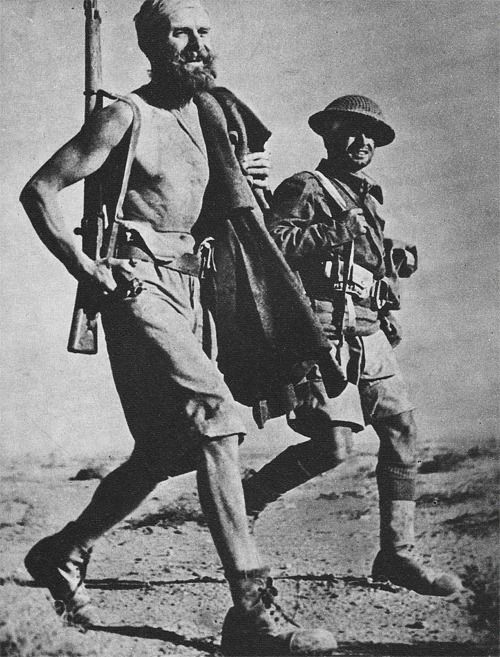 Battle-hardened veterans of Montgomery's Desert Rats stride along a desert track.  The British troops who defeated Rommel in North Africa came from virtually every corner of the Empire; Englishmen fought alongside wiry Gurkhas from Nepal and bearded Sikhs from India, as well as Scots, Canadians, Australians, South Africans and New Zealanders.