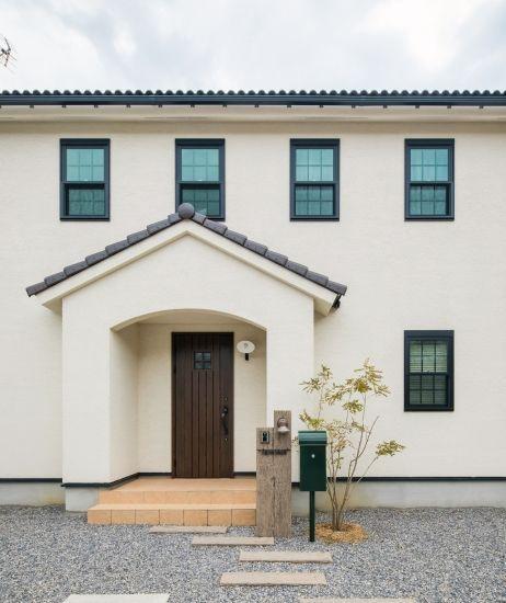 水色のドアと自然素材のキッチンカウンターがかわいい家