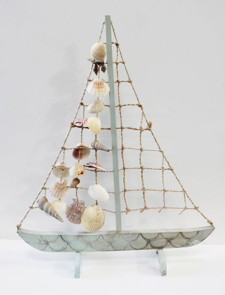 "Sea foam green colored sailboat with rope & seashells for a sail measures 18"" x 14 1/2""."