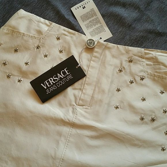 New! NWT! VERSACE JEANS COUTURE Silk Mini New with tags. Versace Jeans Couture 100% silk white mini skirt with back pockets and adorned with silver stars. This is incredible! Never worn. Wrinkly a bit, no biggie. Perfect condition. There is a CERTIFICATE OF AUTHENTICITY AND A SECURITY STRIP SEWN INTO THE TAG. GORGEOUS! Hang onto this forever! Versace Skirts Mini