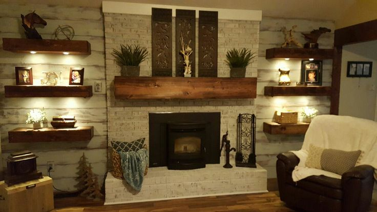 Distressed shiplap siding, distressed floating shelves and mantle with dimmable can lights, whitewashed fireplace.