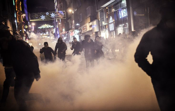 People run away from tear gas and water cannon during clashes between riot-police and prostestors after the funeral of Berkin Elvan, the 15-year-old boy who died from injuries suffered during last year's anti-government protests, in Istanbul on March 12, 2014.