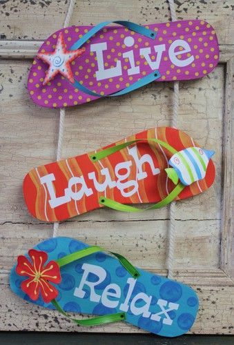 """Triple flip flop sandal sign with the saying """"Live, Laugh, Relax"""" is adorned with fun patterns, a starfish, fish and hibiscus flower."""
