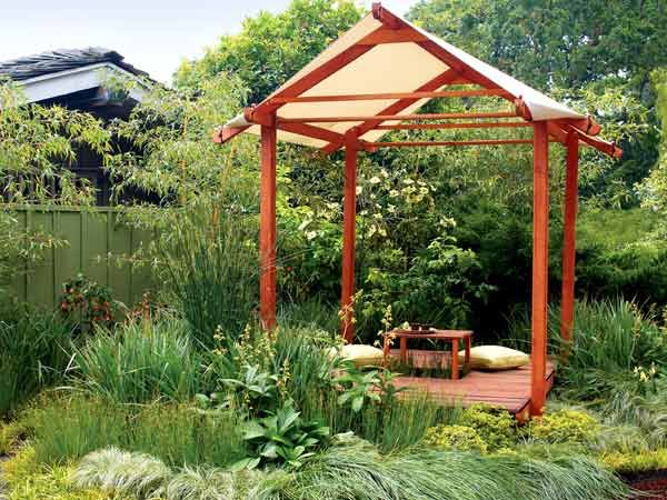 """Inspired by pavilions in Bali, architect Tony Gwilliam's basic T House is the focal point of a """"meditation meadow."""" The simple structure, which consists of a 6- by 10-foot redwood deck, 8-foot Douglas fir posts, a pop-up table, and a marine fabric roof, took two people less than a day to assemble from a kit. (Photo: Thomas J. Story)"""