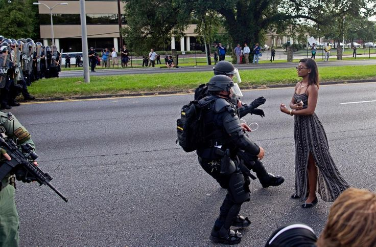 A protester is grabbed by police officers in riot gear after she refused to get off the street in front of the the Baton Rouge Police Department Headquarters in Baton Rouge, Louisiana, on Saturday. Several hundred protesters, including members of the New Black Panther party, blocked the roadway, causing cops to close the road and move the crowd with riot police. Several were arrested.