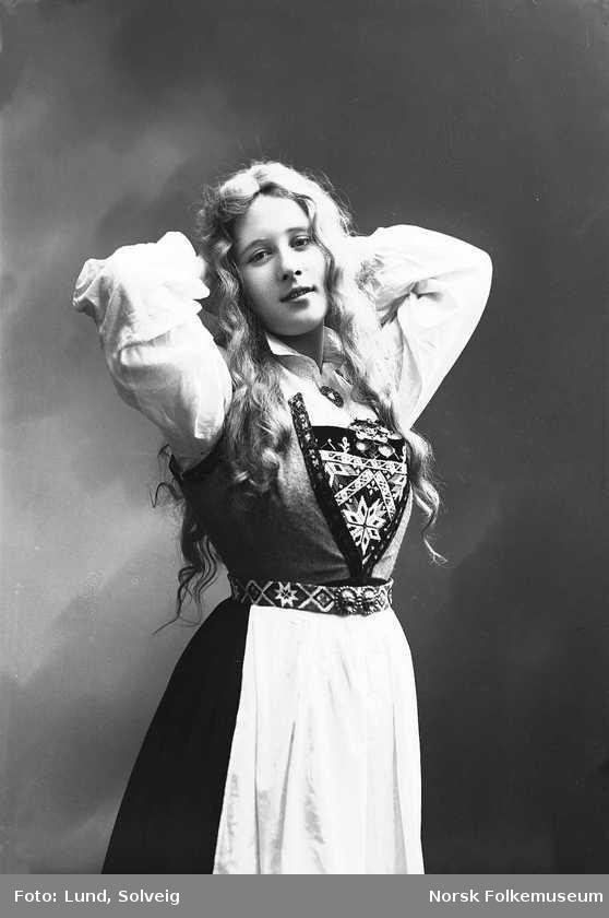 Digitalt Museum - Studioportrett av kvinne i drakt med slett hår og armene bak hodet. Fotograf: Solveig Lund