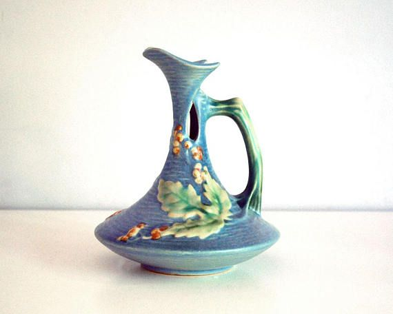 Lovely vintage 1940s Roseville art pottery ewer / pitcher in the Bushberry pattern, with raised leaves and berries on a blue background. The ewer has a graceful spout with a cutout on both sides, just below the branch-like handle. The body of it flairs out and has a textured background, like water, with leaves and berries on both sides.  This fine art ceramic piece dates to 1941. The bottom is marked in relief Roseville U.S.A., with the shape number 1-6. The ewer is in very good conditio...