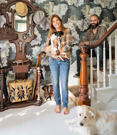 The owners — with rescue pups Mr. Chips and Baxter — wallpapered their hallway in Trove's faded floral.   - CountryLiving.com