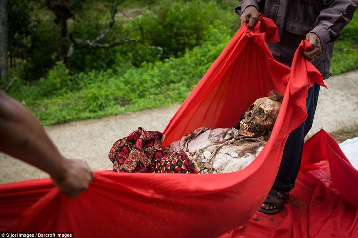 Locals carefully maneuver a corpse before delicately grooming them and dressing…