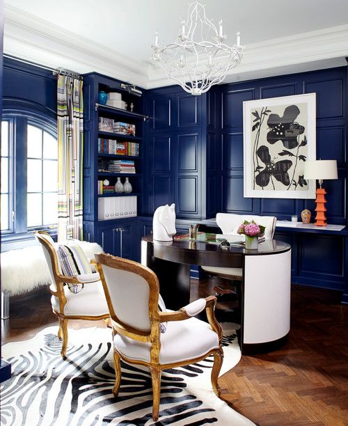A posh eclectic home office with blue lacquered walls and a zebra-print rug