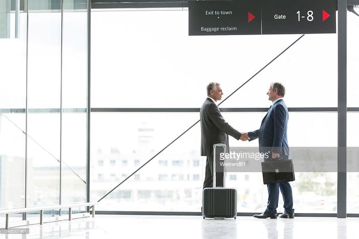 Stock Photo : Two businessmen shaking hands at gate at the airport