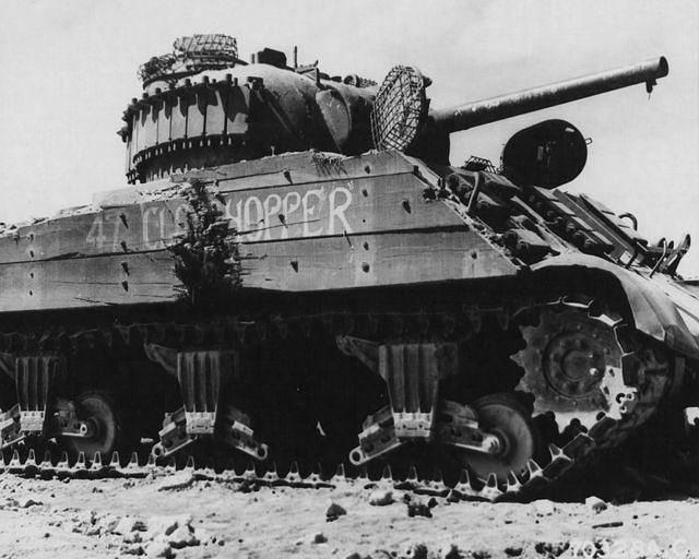 A wrecked Sherman tank, which was momentarily stopped by a direct hit and was burned by Molotov cocktails when Japs crept up on it. The terrain on Iwo Jima in the Bonin Islands made tanks ineffective to a great extent, 15 March 1945.