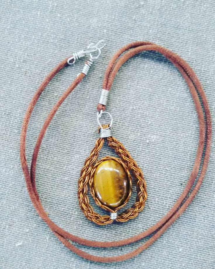colar em cobre vermelho com detalhes detalhes em aço inox, cordão de seda.  Pedra olho de tigre.