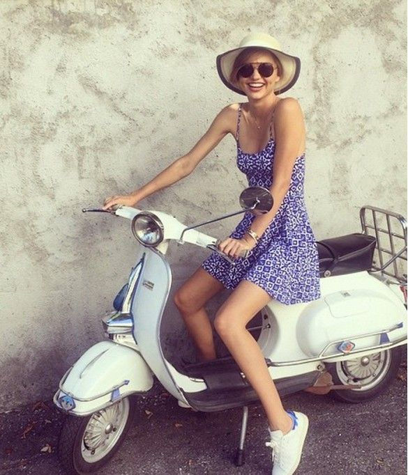 Miranda Kerr wears a blue and white printed sundress, Isabel Marant white sneakers, and a straw sunhat