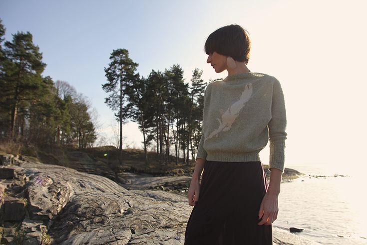Tynn og elegant genser med en stor fjær midt på i pusete angora. Se våre mange fine garnpakker med mønster inkludert.