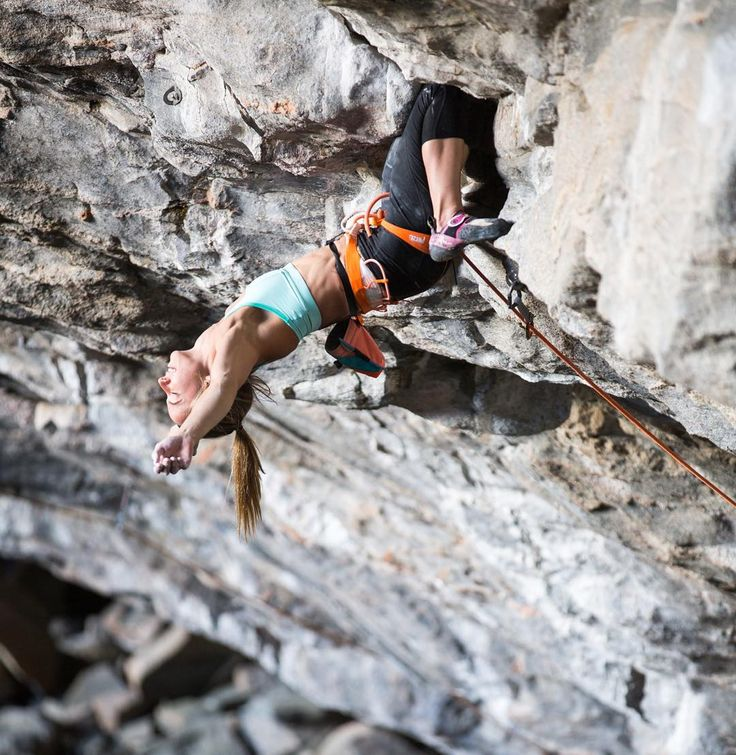 Rock climber Courtney Woods rests her arms during a climb in Flatanger Norway