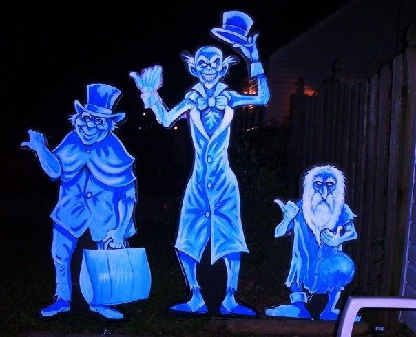 some pink foam life size cut outs painted to look like disneys haunted mansion hitchhiking ghost disney halloween decorationshalloween