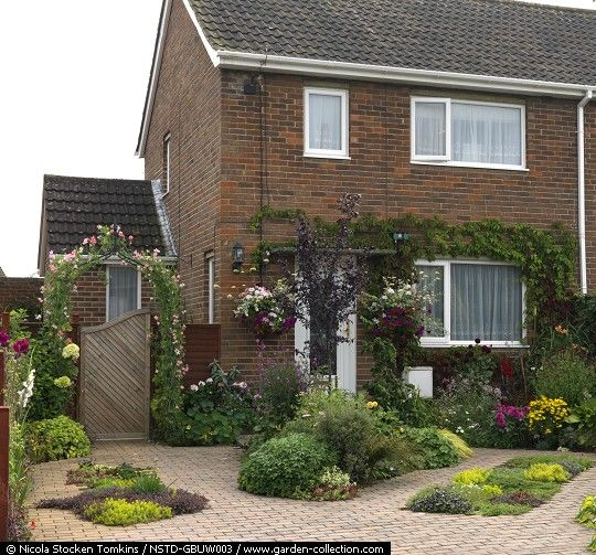 Small front garden is paved for off-street parking, with beds of low-growing…