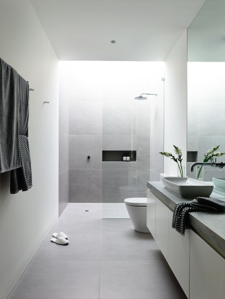 A modern bathroom in a light color pallet featuring light gray tile and a slightly curved rectangular vessel sink. A skylight above the glass-wrapped shower stall provides ample lighting for the room.