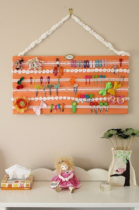 Cutesy white ribbons strung across a bright orange board gives clips and bows a colorful, yet organized, home. See more at Firefly Creative Design