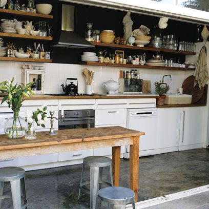 Wooden table with metal bar stools in kitchen - am definitely loving the shelves with dark background